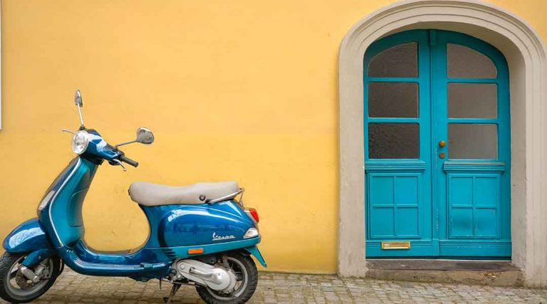 A blue vespa with a yellow background