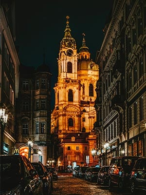 Center of Prague with cars and a lightened Church