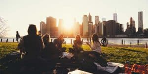 Vrienden die in het park zitten en een picnic hebben bij de ondergaande zon