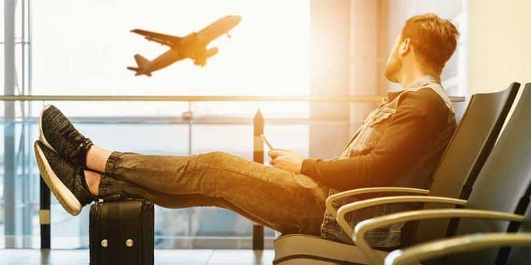 Een jongen die op het vliegveld zit met zijn benen op een koffer
