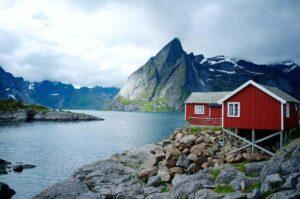 Huisje aan een meer met bergen tijdens een stage in Noorwegen