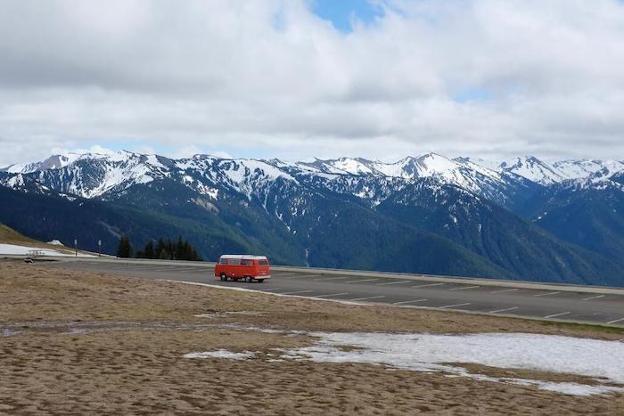Een rode camper die rijdt door de bergen in olympic national park