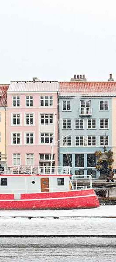 Een fietser langs een boot en gekleurde huizen tijdens een stage in Denemarken